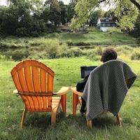 Un homme assis sur une chaise Muskoka avec son ordinateur portatif, devant une rivière.
