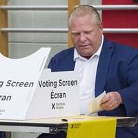 Photo de Doug Ford en train de voter derrière l'isoloir.