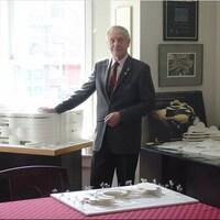 Un homme pose dans un bureau près de maquettes de bâtiments.