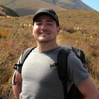 Brian Nadler, lors d'une randonnée en montagne, avec un sac à dos, sourit à la caméra.