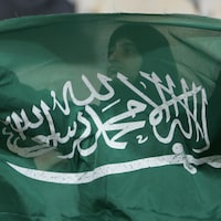Une femme voilée tient un drapeau de l'Arabie saoudite dans ses mains devant elle. On la voit en transparence à travers le tissus du drapeau.
