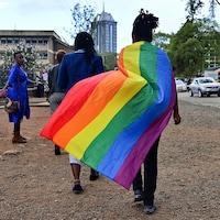 Une personne kenyane, que l'on voit de dos, porte un drapeau arc-en-ciel en guise de cap, et marche sur la voie publique, où se trouvent d'autres personnes.