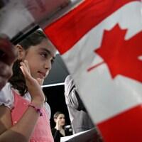 Une petite fille prête serment dans une cérémonie d'octroi de la citoyenneté canadienne, avec un drapeau canadien à l'avant-plan.