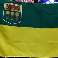 Un drapeau de la Saskatchewan, tenu par plusieurs personnes.