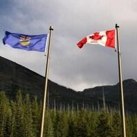 Trois drapeaux côte à côte dans le vent : un de l'Alberta, un du Canada et un de la Colombie-Britannique.
