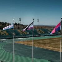 Quatre drapeaux ayant rapport aux réalités LGBTQ2+ flottant dans les airs au stade de l'Université de Sherbrooke.