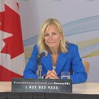 Heather Morrison assise à une table devant un drapeau du Canada et un drapeau de l'Île-du-Prince-Édouard.