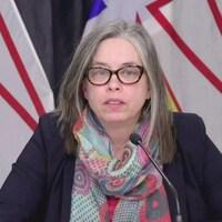 Janice Fitzgerald assise devant des drapeaux de Terre-Neuve-et-Labrador.