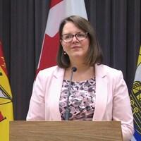 Jennifer Russell au micro, entre deux drapeaux du Nouveau-Brunswick.