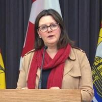 Jennifer Russell en conférence de presse devant des drapeaux du Nouveau-Brunswick.