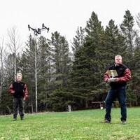 Bruce MacPherson et Darren Clarke une télécommande à la main sont debout alors qu'un drone vole au dessus de leur têtes.