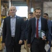 Jean-Yves Duclos et Joel Lightbound en compagnie du maire de Lévis, Gilles Lehouillier. Tous les trois marchent avec des hommes en complet derrière eux. Ils sont dans une usine.