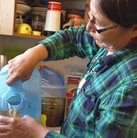 Une femme remplit un verre d'eau