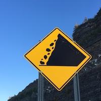 Un panneau de signalisation jaune et noir indiquant un danger de chute de pierres. En arrière-plan, une paroi rocheuse.