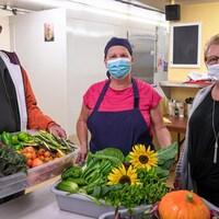 Trois personnes posent pour la caméra dans une cuisine. Ils tiennent dans leur mains des bacs remplis de légumes frais.