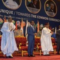 Des dirigeants d'Afrique de l'Ouest applaudissent, debout sur une tribune.