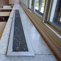 Une bouche de ventilation, devant des fenêtres.