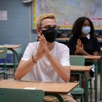 Deux élèves qui portent un masque en classe