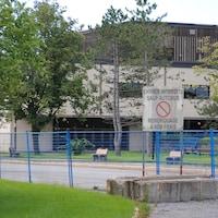 La façade de l'École secondaire Mont-Bleu en été derrière des barrières.