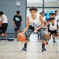 Un jeune homme fixe la caméra en driblant un ballon de basketball.