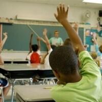 Des enfants assis sur leur chaise dans la classe lèvent la main