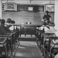 Des élèves, garçons et filles, sont assis à des pupitres (de dos) devant une religieuse qui tient un livre ouvert à l'avant de la classe.