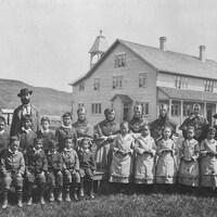 Photo d'archive où l'on voit des élèves et leurs superviseurs regroupés sur le terrain devant l'édifice. Des élèves garçons à gauche, des élèves filles à droite.