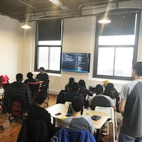 Une photo montrant une salle de classe. Une douzaine d'adolescents sont assis, dos tourné à la caméra, et regardent un téléviseur sur lequel est affiché du code informatique.