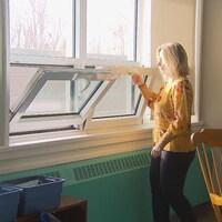 Une femme ouvre des fenêtres.