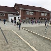 Dans un cour d'école, des enfants à la queue-leu-leu se tiennent loin les uns des autres.