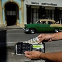 Un homme montre des dollars dans son porte-monnaie dans une rue de La Havane.