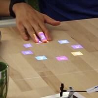 Une photo montrant un bureau sur lequel sont projetées des icônes de couleur, pendant qu'une personne assise touche les projections avec sa main.