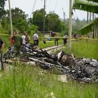 Une carcasse d'avion est vue dans l'herbe, près de rails de train. Des personnes portant une blouse ou des t-shirts se trouvent sur les rails.