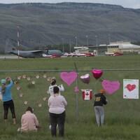 Des personnes accrochent des coeurs sur la clôture d'un aéroport.