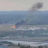 Une colonne de fumée s'échappe d'un avion sur un tarmac dans une photo amateur prise à grande distance.