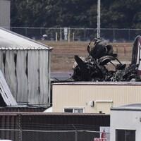 Des débris du vieux bombardier à proximité de bâtiments de l'aéroport.