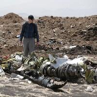 Un homme marche parmi des débris de métal.