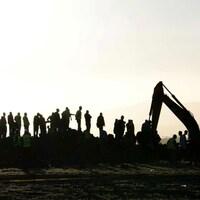 Des personnes observent un tracteur qui creuse le sol sur les lieux d'un écrasement d'avion.