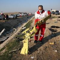 Un membre de l'équipe de secours ramasse un fragment de l'appareil.