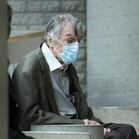 Edgar Fruitier est assis sur un banc et attend.