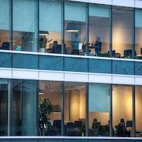 À travers la façade vitrée d'un bâtiment où se trouvent des bureaux, des gens travaillent.