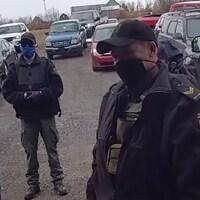 Des policiers dehors devant des voitures portent des masques.