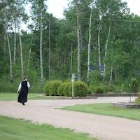 Une femme de dos, vêtue d'une longue robe noire, marche près de l'église.