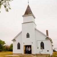 Deux femmes sur le perron d'une petite église blanche, sur un terrain vague.