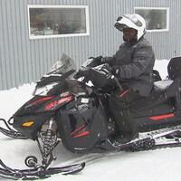 Didier Inongi prend un égoportrait avec son frère Thierry en arrière-plan, assis sur une motoneige.
