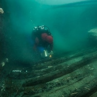 Un plongeur inspecte un ancien navire militaire.