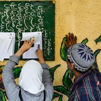 Un Égyptien et une Égyptienne sont à la recherche du bureau de vote où ils pourront remplir le bulletin de vote, dans le nord du Caire, au premier jour d'un scrutin de trois jours.