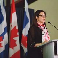 Elle parle à un lutrin devant des drapeaux du Canada et de Toronto.