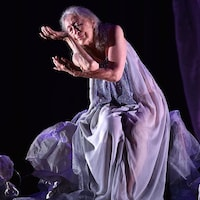 Une femme âgée, vêtue d'une robe mauve, danse sur scène.