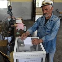 Un homme dépose son bulletin de vote dans l'urne.